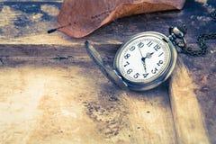 Reloj de bolsillo en el viejo fondo de madera, estilo del vintage Foto de archivo libre de regalías
