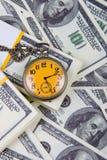 Reloj de bolsillo en una pila de dólares Imagenes de archivo