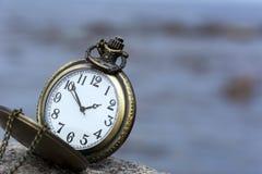 Reloj de bolsillo redondo con la cadena en piedra en el fondo del cielo con Imagen de archivo