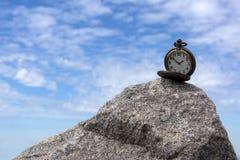 Reloj de bolsillo redondo en una piedra contra el cielo Foto de archivo