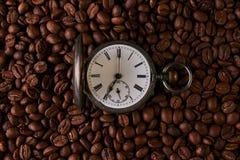 Reloj de bolsillo viejo del vintage en granos de café asados Foto de archivo libre de regalías