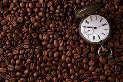 Reloj de bolsillo viejo del vintage en granos de café asados Fotos de archivo libres de regalías