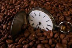Reloj de bolsillo viejo del vintage en granos de café asados Fotografía de archivo