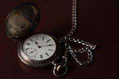 Reloj de bolsillo viejo encima de una caja de madera Foto de archivo libre de regalías