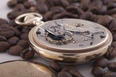 Reloj de bolsillo y granos de café viejos en fondo de la materia textil foto de archivo