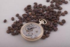 Reloj de bolsillo y granos de café viejos en fondo de la materia textil fotos de archivo