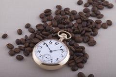 Reloj de bolsillo y granos de café viejos en fondo de la materia textil imagenes de archivo