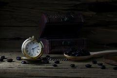 Reloj de bolsillo y granos de café en la madera oscura, aún vida Imagen de archivo libre de regalías