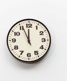 Reloj de Brown en la pared blanca de la oficina cerca del mediodía foto de archivo