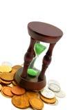 Reloj de la arena y fondo de monedas fotos de archivo