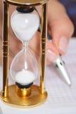 Reloj de la arena y mano de la hembra con la pluma Imagen de archivo libre de regalías