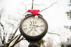 Reloj de la calle del vintage con el sombrero de la Feliz Año Nuevo NYC y de Santa Claus de la inscripción en ellos al aire libre Foto de archivo libre de regalías