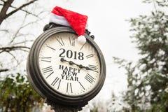Reloj de la calle del vintage con el sombrero de la Feliz Año Nuevo 2018 y de Santa Claus de la inscripción en ellos Fotos de archivo
