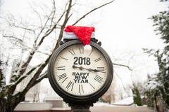Reloj de la calle del vintage con el sombrero de la Feliz Año Nuevo 2018 y de Santa Claus de la inscripción en ellos Imagen de archivo libre de regalías