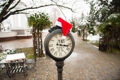 Reloj de la calle del vintage con el sombrero de la Feliz Año Nuevo 2018 y de Santa Claus del texto en ellos en la calle del invi Imagenes de archivo