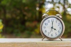 Reloj de la campana del vintage en una cerca de madera con el follaje de otoño en los vagos Imágenes de archivo libres de regalías