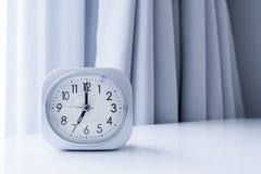 Reloj de la casilla blanca en el soporte blanco de la cama con el fondo blanco de la cortina, tiempo de mañana en la decoración m Foto de archivo