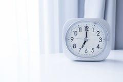 Reloj de la casilla blanca en el soporte blanco de la cama con el fondo blanco de la cortina, tiempo de mañana en la decoración m Imagen de archivo libre de regalías