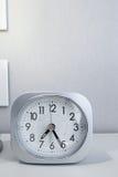 Reloj de la casilla blanca en el soporte blanco de la cama con el fondo blanco del papel pintado, tiempo de mañana en la decoraci Foto de archivo