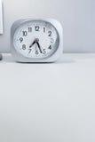 Reloj de la casilla blanca en el soporte blanco de la cama con el fondo blanco del papel pintado, tiempo de mañana en la decoraci Imagen de archivo