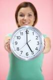 Reloj de la explotación agrícola de la mujer que muestra 5 hora Imágenes de archivo libres de regalías