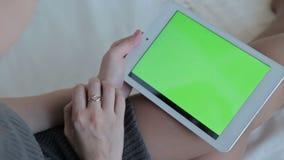 Reloj de la mujer en la tableta verde de la pantalla almacen de metraje de vídeo