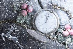 Reloj de la Navidad con la decoración del invierno en nieve Concepto de la Feliz Año Nuevo Fotografía de archivo