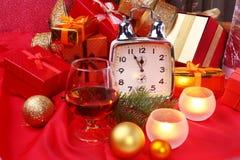 Reloj de la Navidad, vidrio con el coñac o whisky y velas Decoración del ` s del Año Nuevo con las cajas de regalo, las bolas de  Foto de archivo libre de regalías