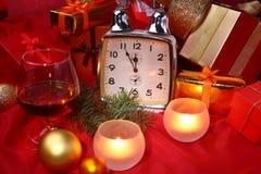 Reloj de la Navidad, vidrio con el coñac o whisky y velas Decoración del ` s del Año Nuevo con las cajas de regalo, las bolas de  Imagen de archivo