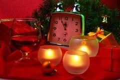 Reloj de la Navidad, vidrio con el coñac o whisky y velas Decoración del ` s del Año Nuevo con las cajas de regalo, las bolas de  Foto de archivo