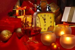 Reloj de la Navidad, vidrio con el coñac o whisky y velas Decoración del ` s del Año Nuevo con las cajas de regalo, las bolas de  Fotografía de archivo libre de regalías