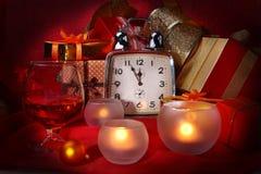 Reloj de la Navidad, vidrio con el coñac o whisky y velas Decoración del ` s del Año Nuevo con las cajas de regalo, las bolas de  Imagenes de archivo