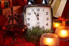Reloj de la Navidad, vidrio con el coñac o whisky y velas Decoración del ` s del Año Nuevo con las cajas de regalo, las bolas de  Fotos de archivo libres de regalías
