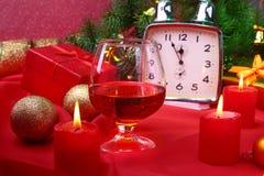 Reloj de la Navidad, vidrio con el coñac o whisky y velas Decoración del ` s del Año Nuevo con las cajas de regalo, las bolas de  Fotografía de archivo