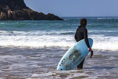 RELOJ DE LA PERSONA QUE PRACTICA SURF ADENTRO AL OCÉANO fotografía de archivo