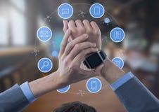 Reloj de la tenencia del hombre de negocios con los iconos de los apps en sitio grande Foto de archivo libre de regalías