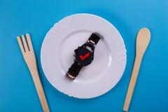 Reloj de la visión superior en un plato foto de archivo libre de regalías