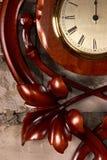 Reloj de madera tallado en la pared de ladrillo Foto de archivo