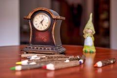 Reloj de madera viejo y l?pices coloreados imagen de archivo libre de regalías