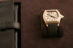 Reloj de oro con la correa negra Fotos de archivo