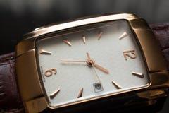 Reloj de oro del ` s de los hombres en un fondo negro Imagen de archivo libre de regalías