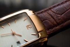 Reloj de oro del ` s de los hombres en un fondo negro Foto de archivo libre de regalías