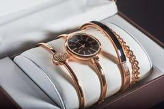 Reloj de oro del ` s de las mujeres en un fondo blanco Imagen de archivo libre de regalías