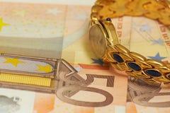 Reloj de oro en el dinero Foto de archivo
