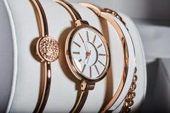 Reloj de oro de la mujer en un fondo blanco en la caja Fotografía de archivo libre de regalías