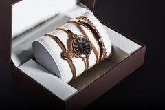 Reloj de oro de la mujer en un fondo blanco en la caja Imagenes de archivo