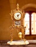 Reloj de péndulo de cobre amarillo de oro de la vendimia antigua Fotografía de archivo libre de regalías