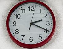 Reloj de pared alrededor del plástico blanco rojo foto de archivo