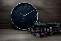 Reloj de pared con las placas de circuito en el fondo de madera, aún vida Foto de archivo