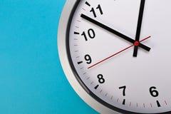 Reloj de pared del primer fijado en fondo azul r imagenes de archivo